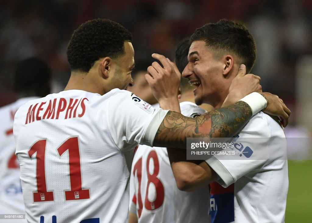 Lyon's forward Houssem Aouar (R) is congratuled by teamate Lyon's Dutch forward Memphis Depay (L) after scoring during the French L1 football match between Dijon FCO and Olympique Lyonnais, on April 20, 2018, at the Gaston Gérard Stadium in Dijon, central France.