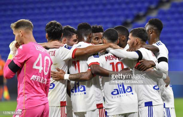 Lyon's forward Houssem Aouar is congratuled by teamates after scoring a goal from the penaltykick as Monaco's French goalkeeper Benjamin Lecomte...
