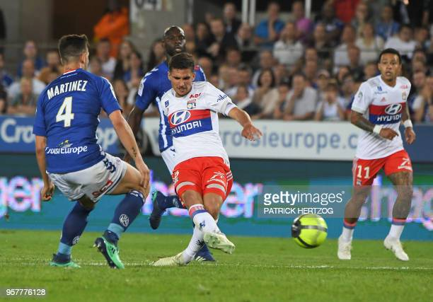 Lyon's forward Houssem Aouar scores a goal despite Strasbourg's French midfielder Pablo Martinez during the French Ligue 1 football match between...