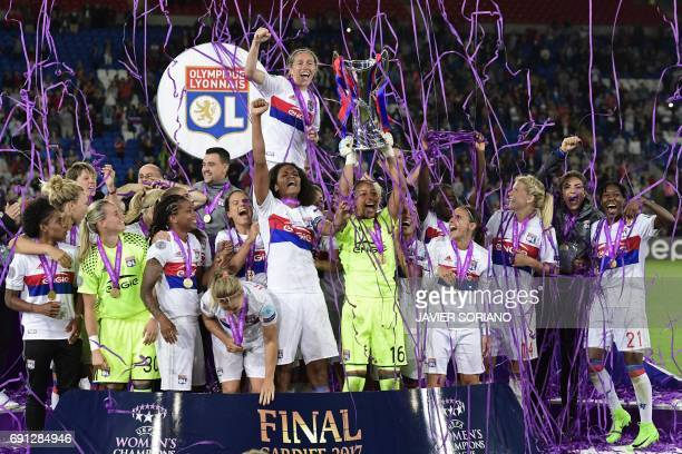 TOPSHOT Lyon's French captain Wendie Renard gestures as Lyon's French goalkeeper Sarah Bouhaddi holds aloft the Women's Champion's League trophy as...