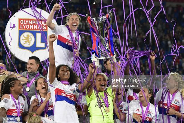 Lyon's French captain Wendie Renard gestures as Lyon's French goalkeeper Sarah Bouhaddi holds aloft the Women's Champion's League trophy as the Lyon...