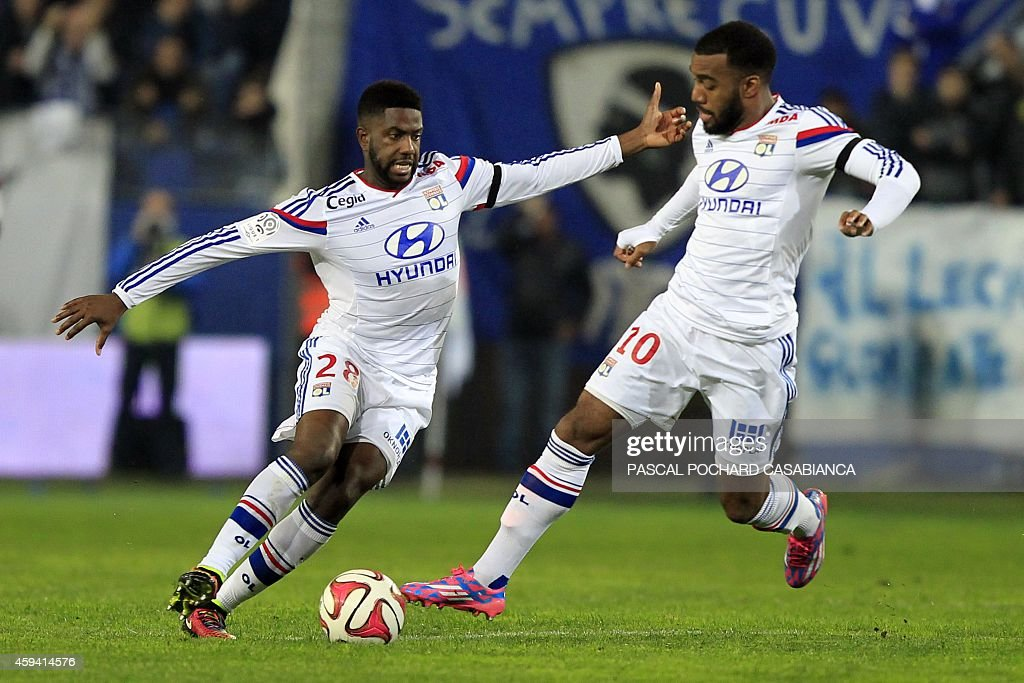 Lyon's French Congolese midfielder Arnold Mvuemba (L) and Lyon's French forward Alexandre Lacazette run with the ball during the French L1 football match Bastia (SCB) against Lyon (OL) on November 22, 2014 in the Armand Cesari stadium in Bastia, French Mediterranean island of Corsica.