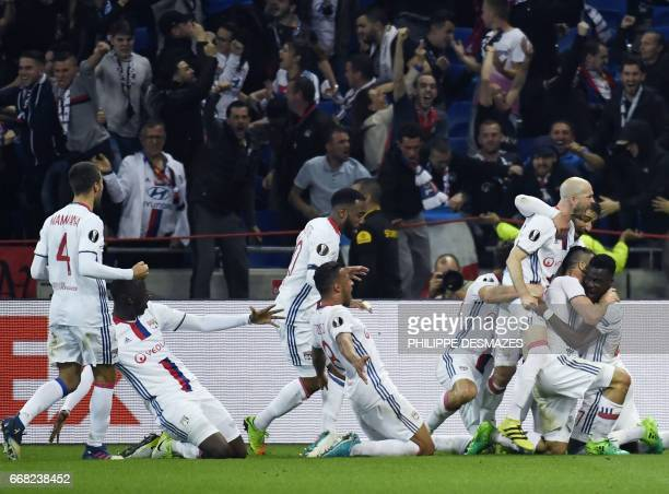 Lyon's French defender Jeremy Morel is congratuled by teamates after scoring a goal during the UEFA Europa League first leg quarter final football...