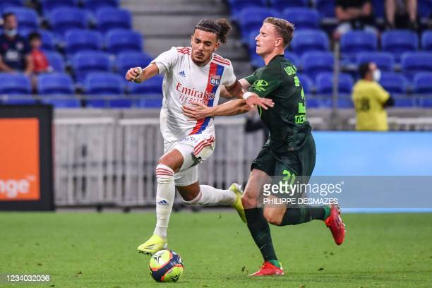 Lyon's French defender Malo Gusto fights for the ball with Wolfsburg's German midfielder Yannick Gerard during the friendly football match between...