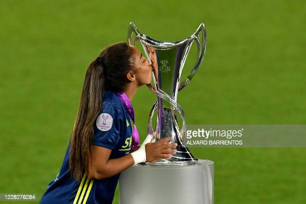 Lyon's French defender Selma Bacha kisses the winner's trophy as she celebrates with teammates after winning the UEFA Women's Champions League final...