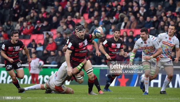 Lyon's French flanker Loann Goujon runs with the ball as he is tackled by Treviso's Italian lock Niccolo Cannone during the European Rugby Champions...