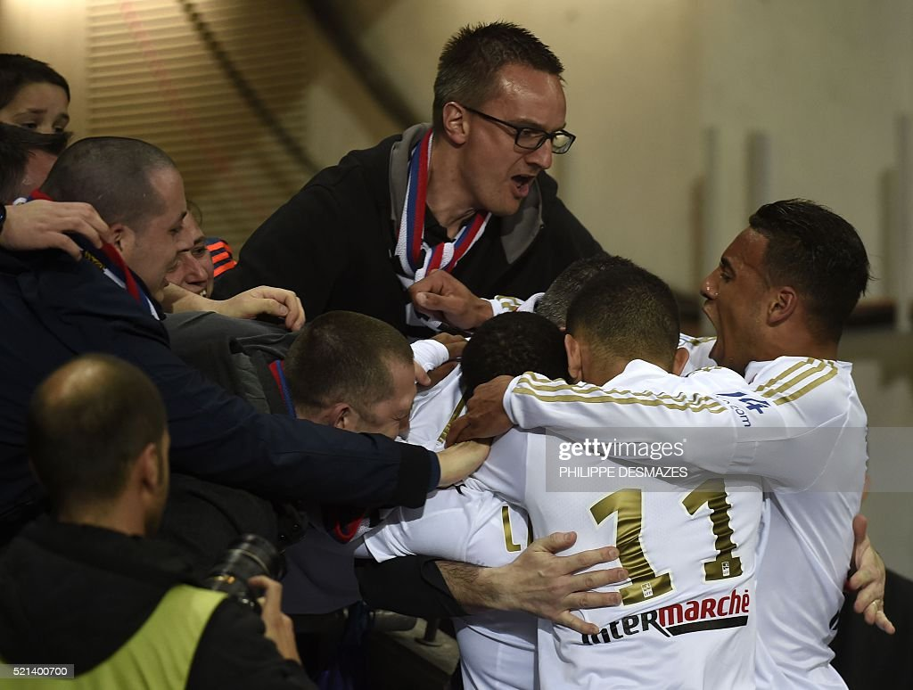 Lyon's French forward Alexandre Lacazette is congratuled by teamates and fans after scoring during the French L1 football match Olympique Lyonnais and OGC Nice on April 15, 2016, at the New Stadium in Decines-Charpieu near Lyon, southeastern France.