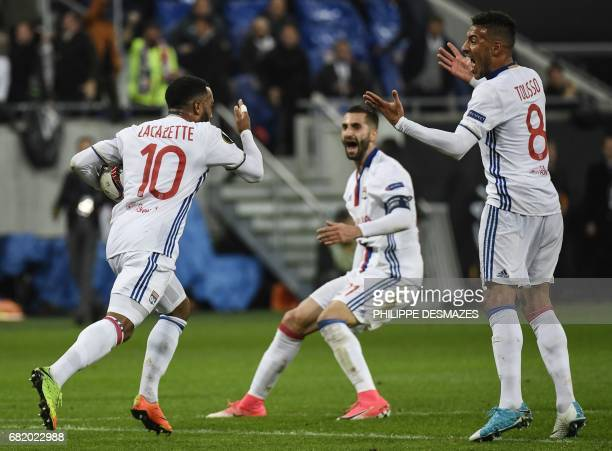 Lyon's French forward Alexandre Lacazette is congratuled by teammates French midfielder Coretin Tolisso and French midfielder Maxime Gonalons after...