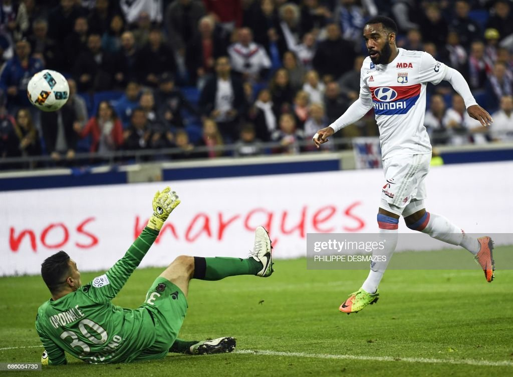 Lyon's French forward Alexandre Lacazette (R) shoots and scores his 100th goal in Ligue 1 past Nice's French goalkeeper Yoann Cardinale during the French L1 football match between Lyon (OL) and Nice (OGCN) on May 20, 2017, at the Parc Olympique Lyonnais stadium in Decines-Charpieu near Lyon, central-eastern France. /