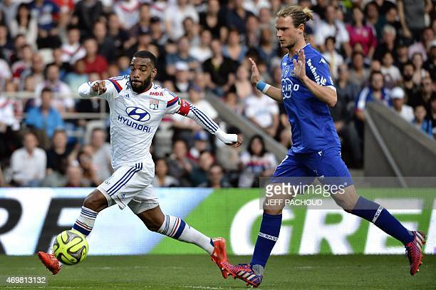Lyon's French forward Alexandre Lacazette vies with Bastia's Belgian midfielder Guillaume Gillet during the French L1 football match Olympique...
