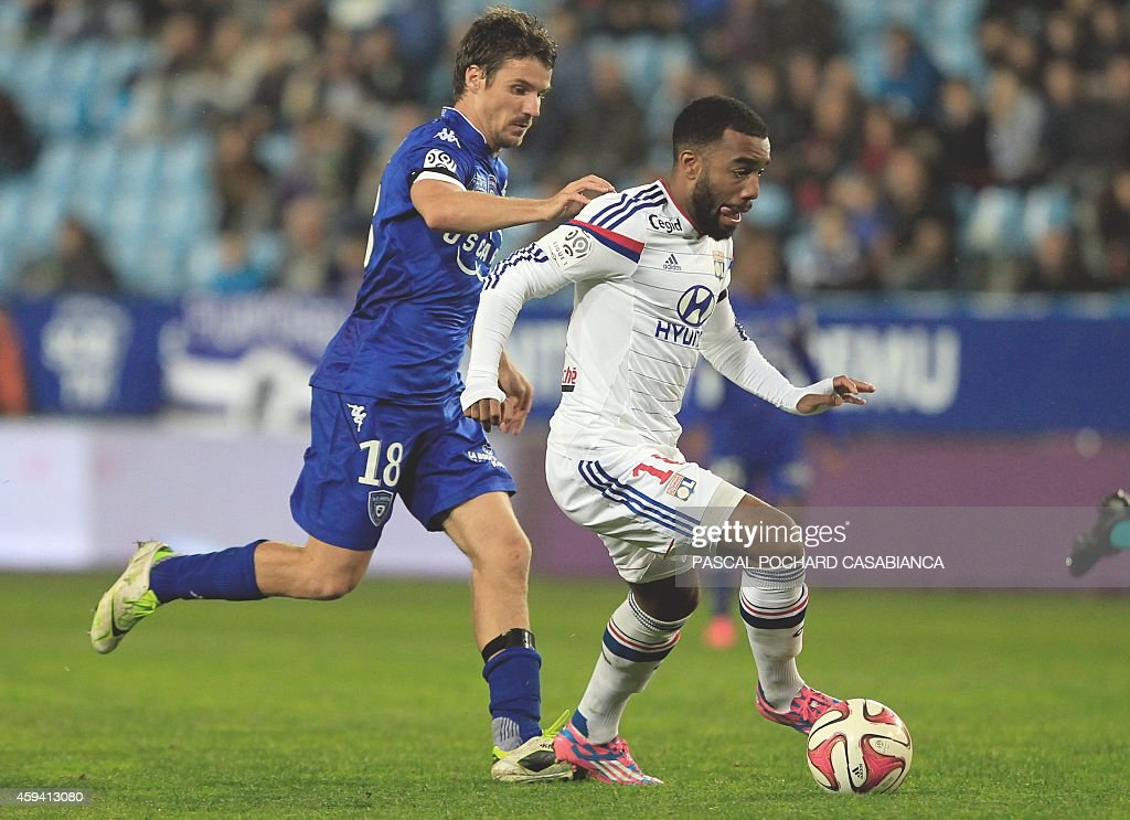 Lyon's French forward Alexandre Lacazette vies with Bastia's French midfielder Yannick Cahuzac during the French L1 football match Bastia (SCB) against Lyon (OL) on November 22, 2014 in the Armand Cesari stadium in Bastia, French Mediterranean island of Corsica.