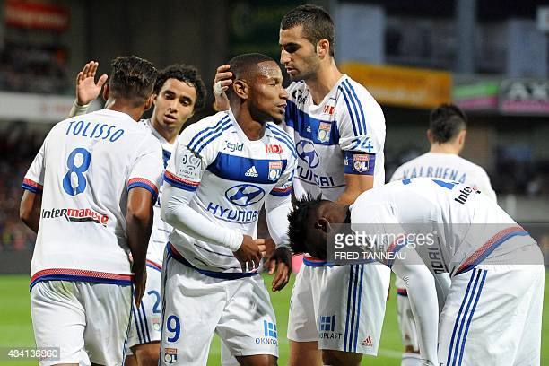 Lyon's French forward Claudio Beauvue is congratulated by his teammates after scoring a goal during the French L1 football match between Guingamp and...