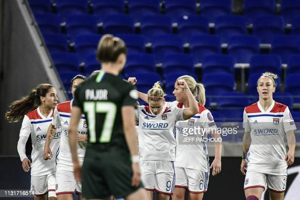 Lyon's French forward Eugenie Le Sommer celebrates with teammates after scoring during the UEFA women's Champions League quarterfinal football match...