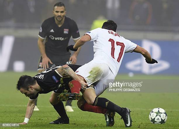 Lyon's French forward Mathieu Valbuena and Sevilla's midfielder Pablo Sarabia fall on the ground during the UEFA Champions League Group H football...