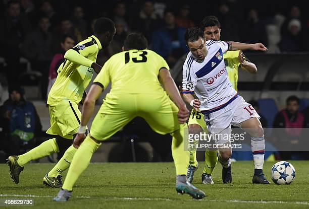 Lyon's French forward Mathieu Valbuena vies for the ball with Gent's Israeli midfielder Kenny Saief and Gent's Serbian defender Stefan Mitrovic...