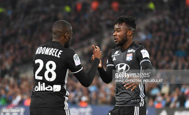 Lyon's French forward Maxwel Cornet celebrates after Olympique de Marseille's French defender Adil Rami scored an own goal during the French L1...