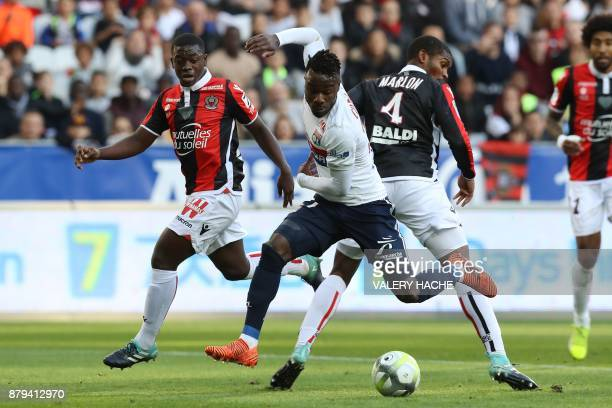 Lyon's French forward Maxwel Cornet fights for the ball with Nice's defender Marlon Santos during the French L1 football match Nice vs Lyon at The...