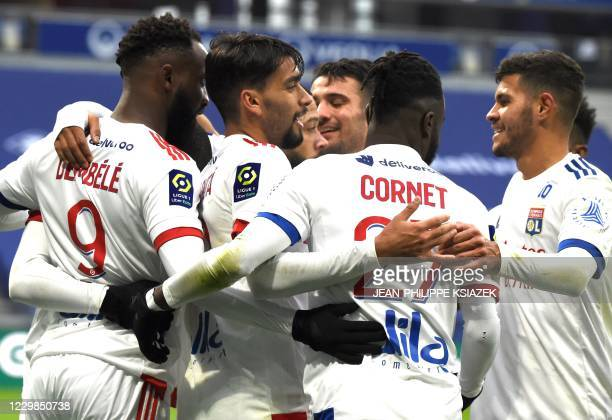 Lyon's French forward Moussa Dembele celebrates with his team after he scored a goal during the French L1 football match between Lyon and Reims on...