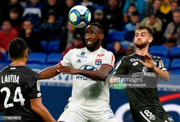 Lyon's French forward Moussa Dembele challenges Dijon's French defender Wesley Lautoa and Dijon's French midfielder Bryan Soumare during the French...