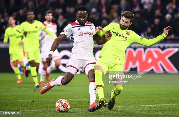 Lyon's French forward Moussa Dembele prepares to shoot the ball next to Barcelona's Spanish defender Gerard Pique during the UEFA Champions League...