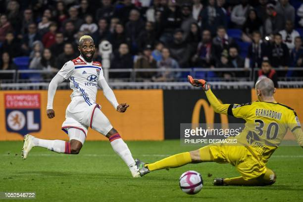 TOPSHOT Lyon's French forward Moussa Dembele vies with Nimes' French goalkeeper Paul Bernardoni during the French L1 football match between Olympique...