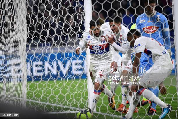 Lyon's French forward Nabil Fekir celebrates is congratulated by teammates after scoring a goal during the French L1 football match between Lyon and...