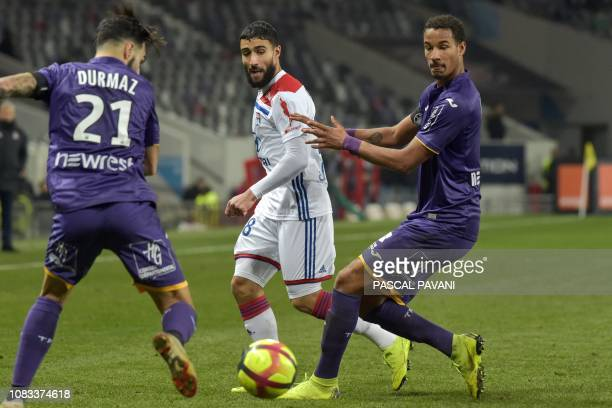Lyon's French forward Nabil Fekir fights for the ball with Toulouse's Swedish midfielder Jimmy Durmaz and Toulouse's French defender Christopher...