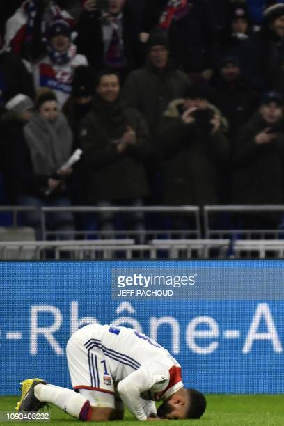 Lyon's French forward Nabil Fekir kisses the field as he jubilates after scoring a goal during the French L1 football match between Olympique...