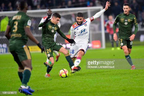 Lyon's French forward Nabil Fekir vies with Reims' French midfielder Mathieu Cafaro during the French L1 football match between Lyon and Reims on...