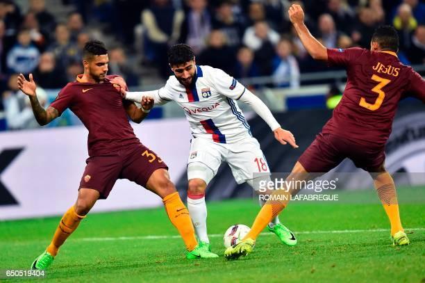 Lyon's French forward Nabil Fekir vies with Romas Brazilian defender Emerson Palmieri and Romas Brazilian defender Juan Jesus Romas Brazilian...