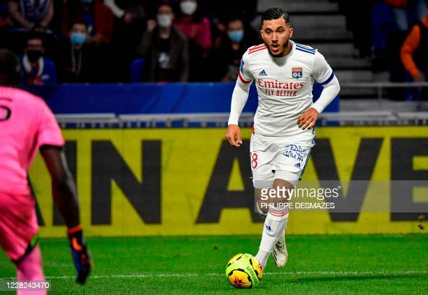 Lyon's French forward Rayan Cherki eyes Dijon's Senegalese goalkeeper Alfred Gomis during the French L1 footall match between Olympique Lyonnais and...