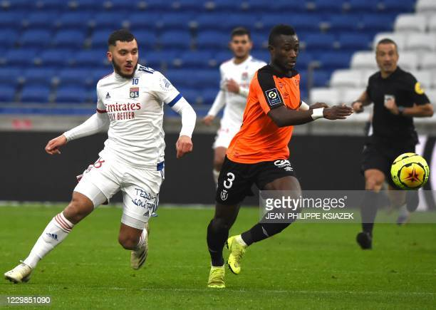Lyon's French forward Rayan Cherki fights for the ball with Reims' Ivoirian defender Ghislain Konan during the French L1 football match between Lyon...