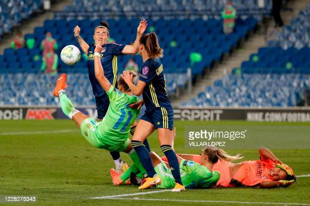 Lyon's French goalkeeper Sarah Bouhaddi holds her head as she falls after colliding with VfL Wolfsburg's Swedish midfielder Fridolina Rolfo during...