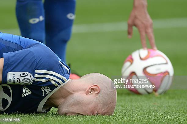 Lyon's French midfielder Christophe Jallet lies on the pitch after a tackle during the French L1 football match between Nantes and LYON on September...