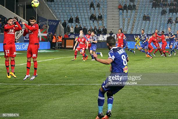 Lyon's French midfielder Corentin Tolisso and Lyon's Algerian forward Rachid Ghezzal head the ball during the French L1 football match between Bastia...