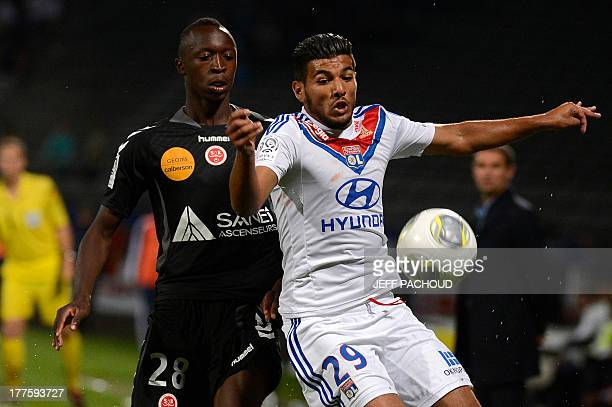 Lyon's French midfielder Fares Balhouli fights for the ball with Reims' defender Antoine Conte during the French L1 football match Olympique Lyonnais...