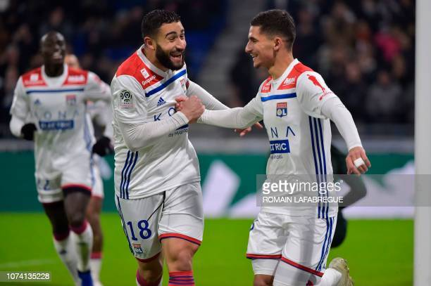 Lyon's French midfielder Houssem Aouar celebrates after scoring a goal with Lyon's French forward Nabil Fekir during the French L1 football match...