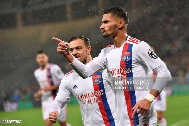 Lyon's French midfielder Houssem Aouar celebrates after scoring a goal next to Lyon's Swiss forward Xherdan Shaqiri during the French L1 football...
