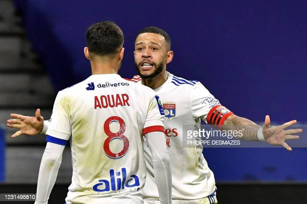 Lyon's French midfielder Houssem Aouar celebrates with Lyon's Dutch forward Memphis Depay after scoring during the French L1 football match between...