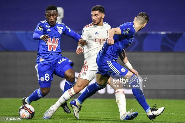 Lyon's French midfielder Houssem Aouar challenges Strasbourg's Ghanaian forward Majeed Waris during the French L1 football match between Olympique...