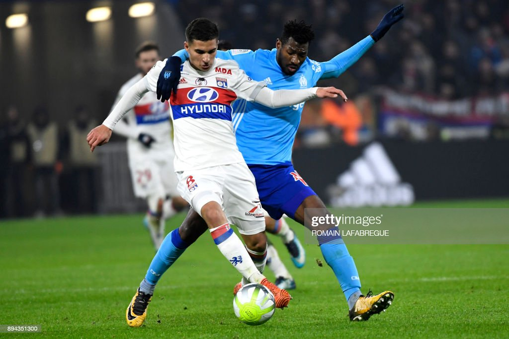 Lyon's French midfielder Houssem Aouar (L) is challenged by Marseille's Cameroonian midfielder Andre-Frank Zambo Anguissa during the French L1 football match between Lyon (OL) and Marseille (OM) on December 17, 2017, at the Groupama stadium in Decines-Charpieu near Lyon, central-eastern France. /