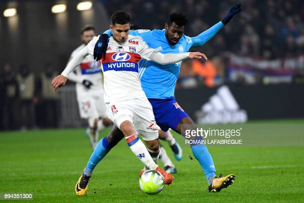 Lyon's French midfielder Houssem Aouar is challenged by Marseille's Cameroonian midfielder AndreFrank Zambo Anguissa during the French L1 football...