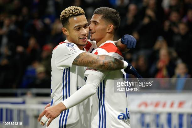 Lyon's French midfielder Houssem Aouar is congratuled by teamate Memphis Depay after scoring a goal during the French L1 football match between...