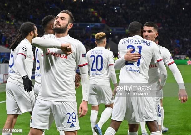 Lyon's French midfielder Lucas Tousart celebrates with teammates after scoring a try during the UEFA Champions League round of 16 first-leg football...