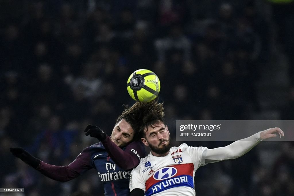 TOPSHOT - Lyon's French midfielder Lucas Tousart (R) heads the ball with Paris Saint-Germain's French midfielder Adrien Rabiot during the French L1 football match between Olympique Lyonnais and Paris-Saint Germain (PSG) at Groupama stadium in Decines-Charpieu on January 21, 2018. /