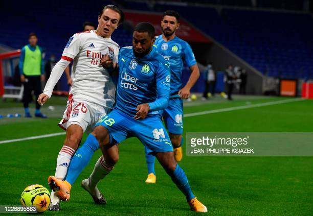 Lyon's French midfielder Maxence Caqueret challenges Marseille's French defender Jordan Amavi during the French L1 football match between Olympique...