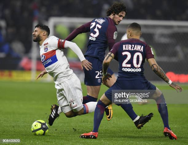 Lyon's French midfielder Nabil Fekir falls next to Paris SaintGermain's French defender Layvin Kurzawa and Paris SaintGermain's French midfielder...