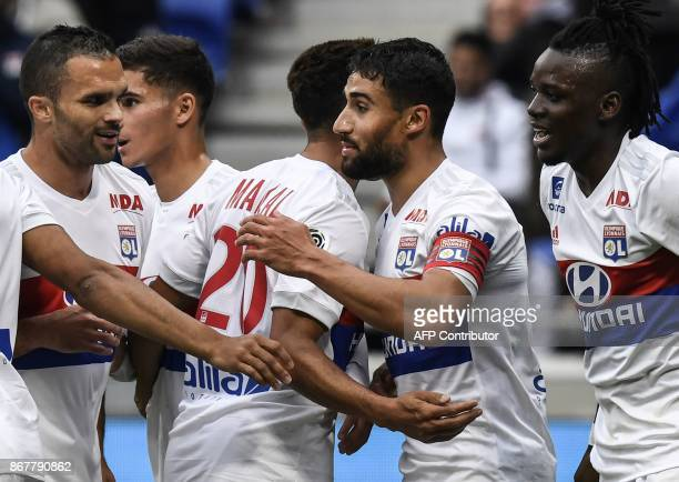 Lyon's French midfielder Nabil Fekir is congratulated by teamates after scoring during the French L1 football match between Olympique Lyonnais and FC...