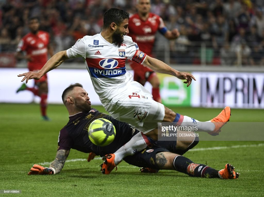 Lyon's French midfielder Nabil Fekir (up) is tackled by Dijon's French goalkeeper Baptiste Reynet (down) during the French L1 football match between Dijon FCO and Olympique Lyonnais, on April 20, 2018, at the Gaston Gérard Stadium in Dijon, central France.