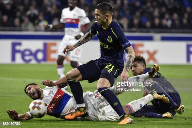 Lyon's French midfielder Nabil Fekir is tackled by Everton's Bosnian midfielder Muhamed Besic and Everton's English defender Mason Holgate during the...